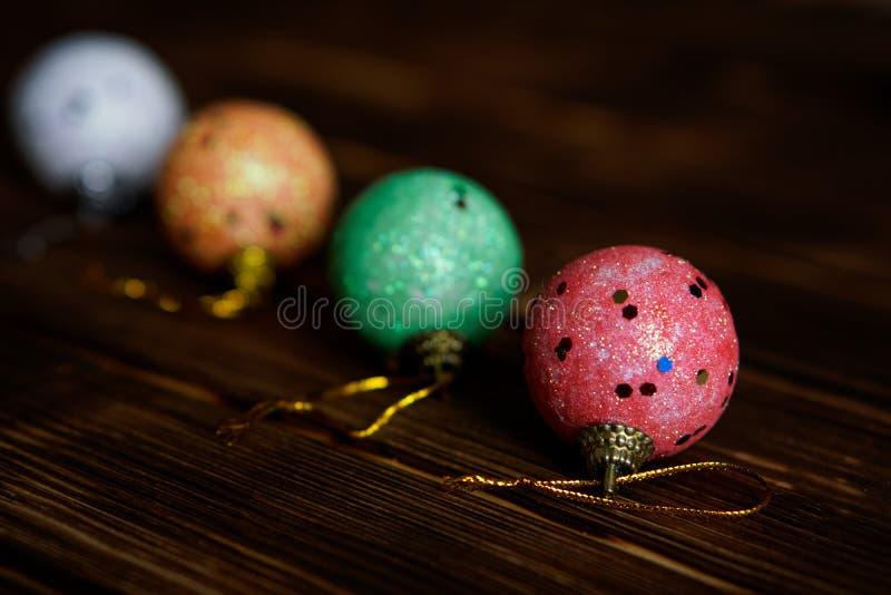 Juguetes de la Navidad - cuatro bolas multicoloras en una oscuridad imagen de archivo