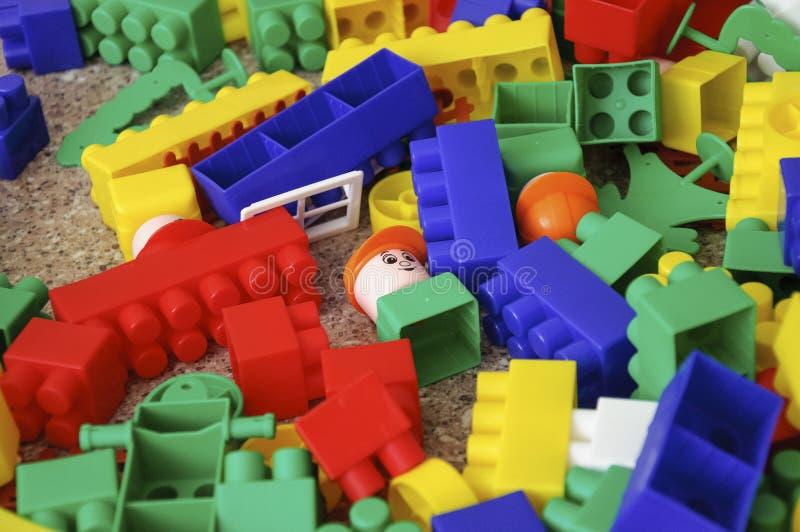 Juguetes de los niños Constructor plástico coloreado multi con los bloques para las casas constructivas y coches, llano, autobús  fotografía de archivo libre de regalías