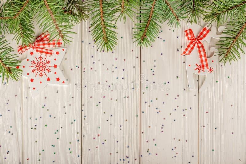 Juguetes de madera de la Navidad en un fondo blanco Ramificaciones Spruce fotografía de archivo libre de regalías