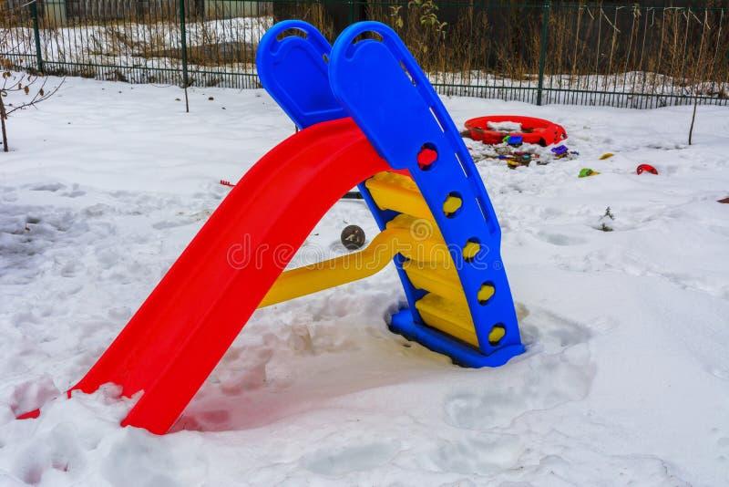 Juguetes del ` s de los niños cubiertos con nieve en la yarda de una casa fotos de archivo libres de regalías