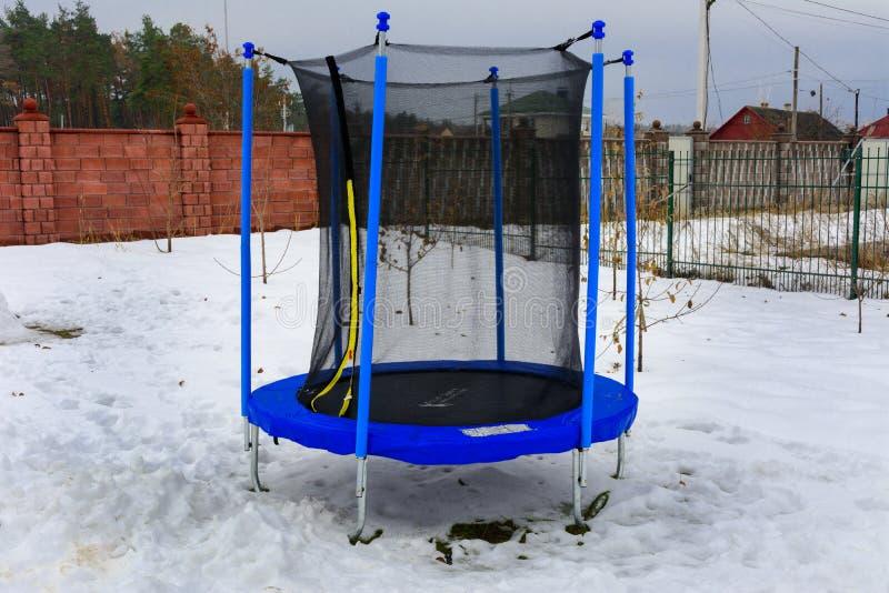 Juguetes del ` s de los niños cubiertos con nieve en la yarda de una casa fotos de archivo