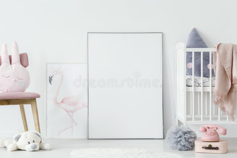 Juguetes en interior del dormitorio del ` s del niño con la cama blanca al lado del po vacío fotografía de archivo