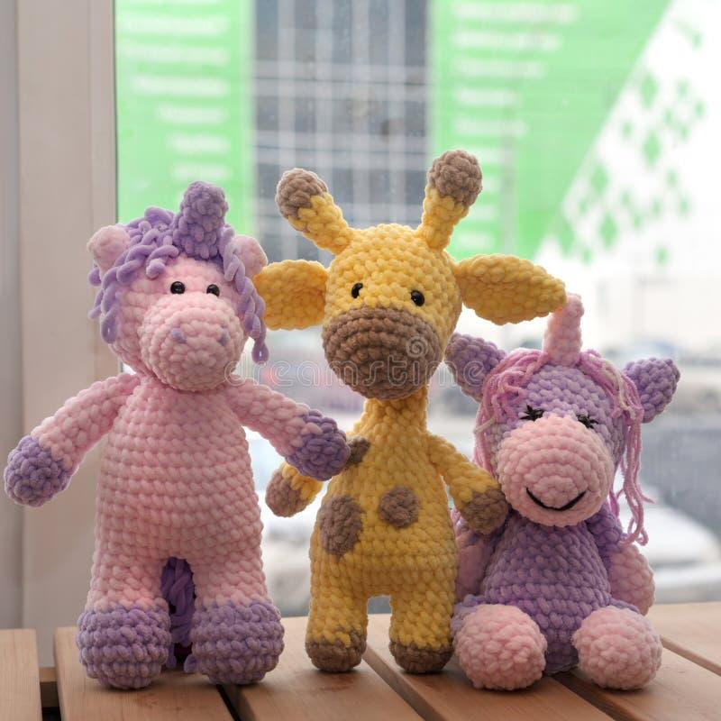 Juguetes hechos punto hechos a mano Jirafa amarilla y dos unicornios foto de archivo libre de regalías