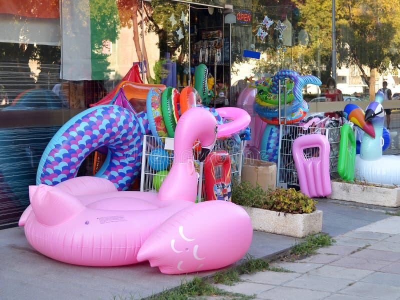 Juguetes inflables de la natación expuestos en la acera cerca de la entrada a la tienda imagen de archivo