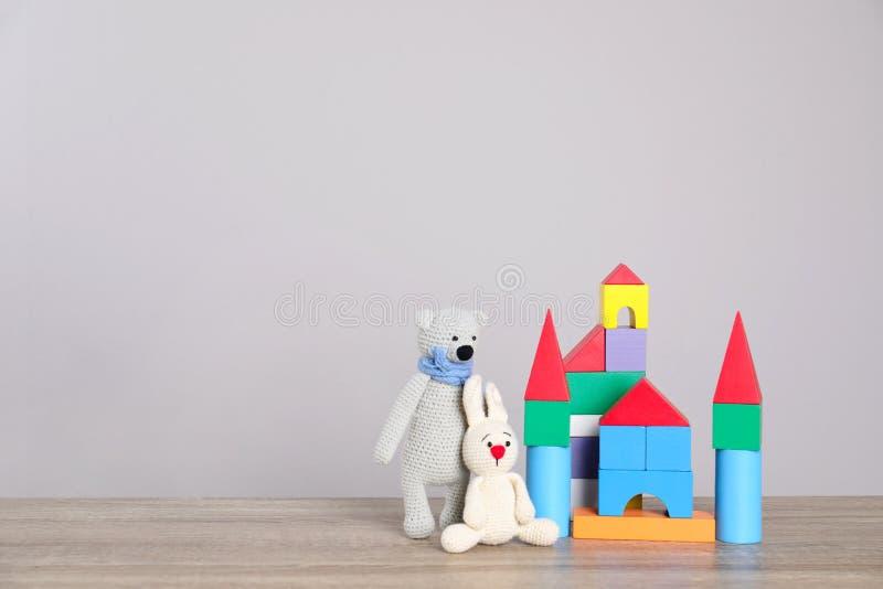 Juguetes lindos y castillo hechos de bloques coloridos en la tabla contra el fondo ligero, espacio para el texto fotografía de archivo