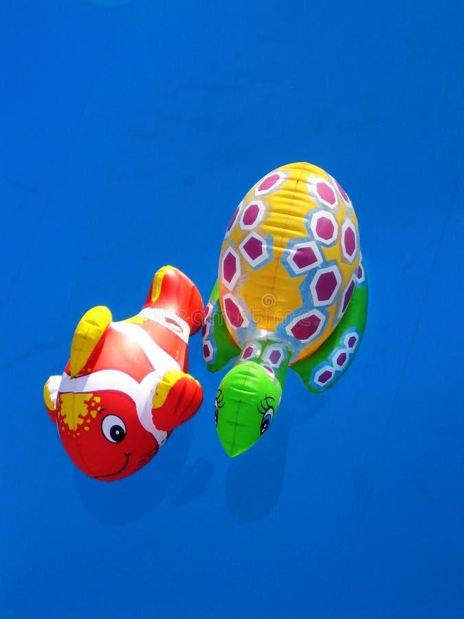 Juguetes que nadan que sorprenden en papel pintado macro del agua azul profunda de la piscina fotografía de archivo libre de regalías