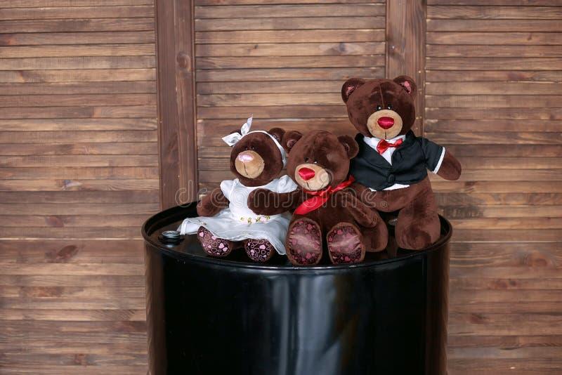 Juguetes suaves, una familia de osos, en un barril de aceite de motor, contra una pared de madera imágenes de archivo libres de regalías