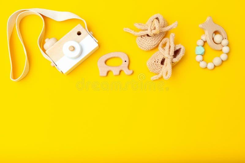 Juguetes y zapatos de bebé de madera en un fondo amarillo Copie el espacio imagen de archivo libre de regalías