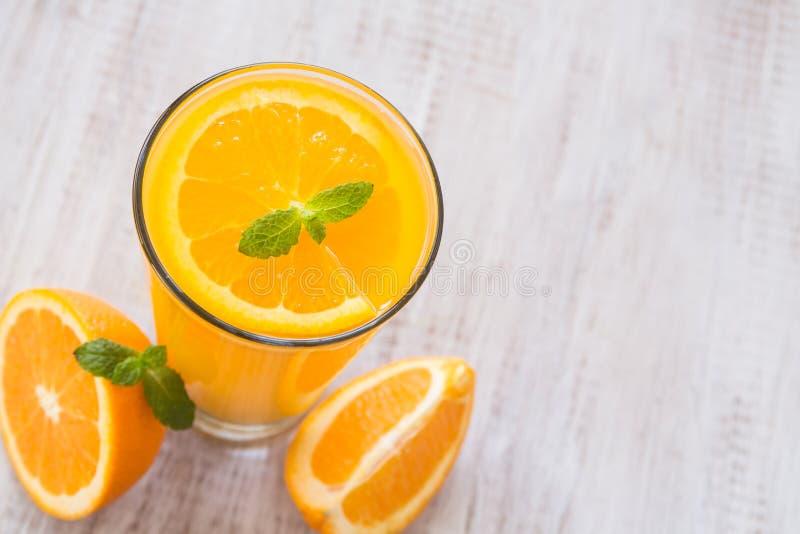 Juice In alaranjado um o vidro com a folha da hortelã de cima de foto de stock royalty free
