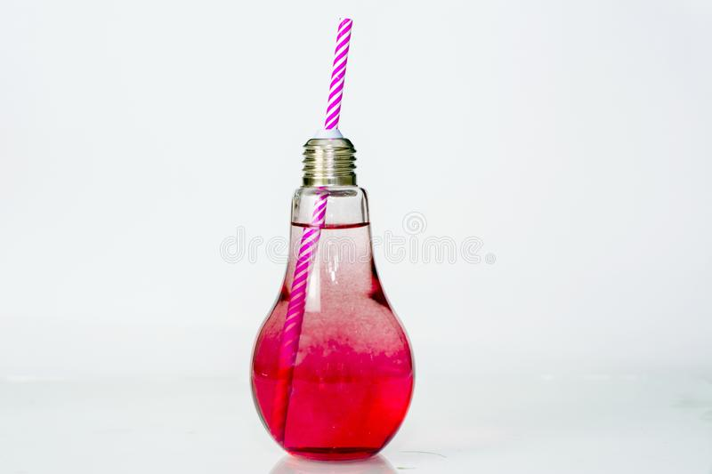 Juice in a clear glass bottle with a white and pink tube, placed on an isolated white background, infused water and healthy drink stock photography