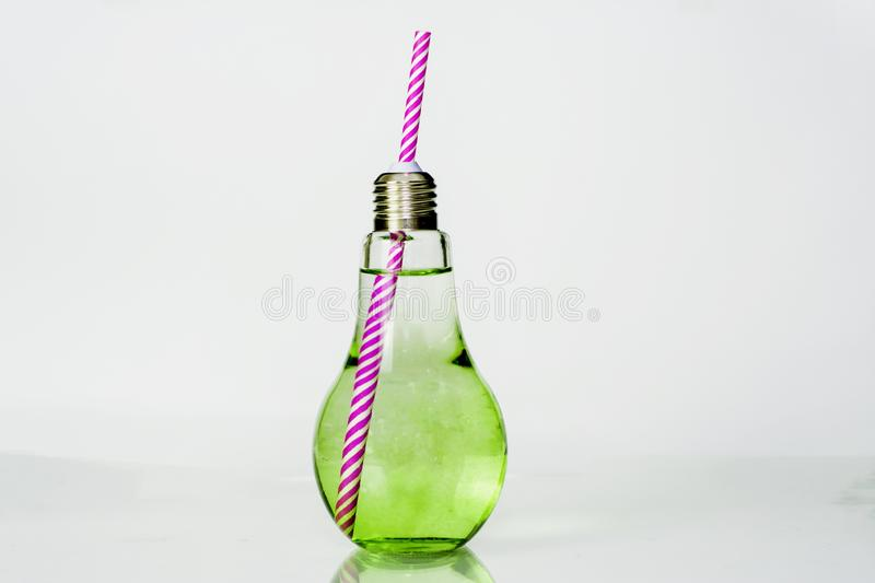 Juice in a clear glass bottle with a white and pink tube, placed on an isolated white background, infused water and healthy drink royalty free stock image