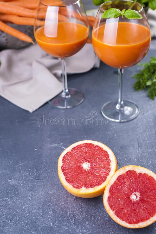 Juice from fresh carrots and basil in a glass, vitamin drink for a healthy diet. Copy space royalty free stock photography