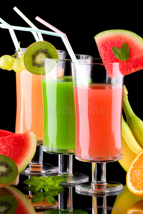 Juice and fresh fruits - organic, health drinks se. Three glasses of organic juice made from fresh fruits and surrounded by fresh ones. Series about organic and royalty free stock photo
