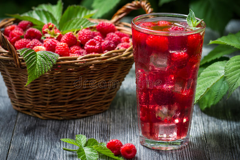 Juice of fresh raspberries served with ice in a glass stock image