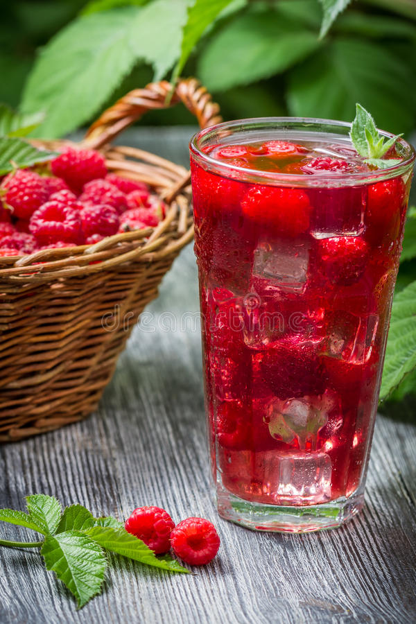 Juice of fresh raspberries served with ice in a glass royalty free stock photo