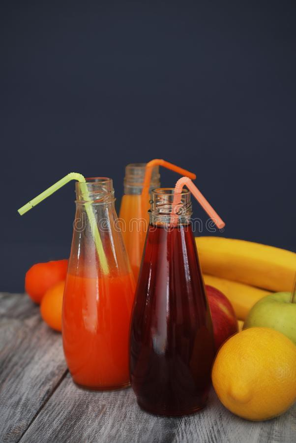 Juice Glasses of freshly Fruit juice with colorful fruits on Rustic Gray wooden Background. Healthy Food Concept. royalty free stock photography