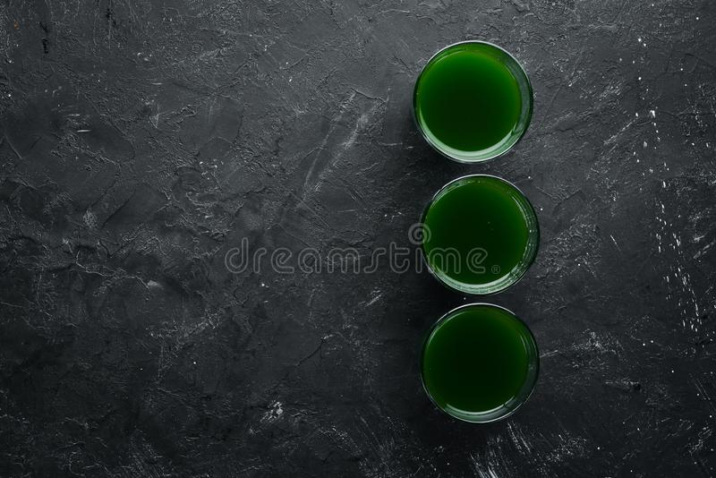 The juice from the green sprouted wheat, and wheat grains. On a black background. Micro Green. Healthy food. Top view. Free space for your text royalty free stock images