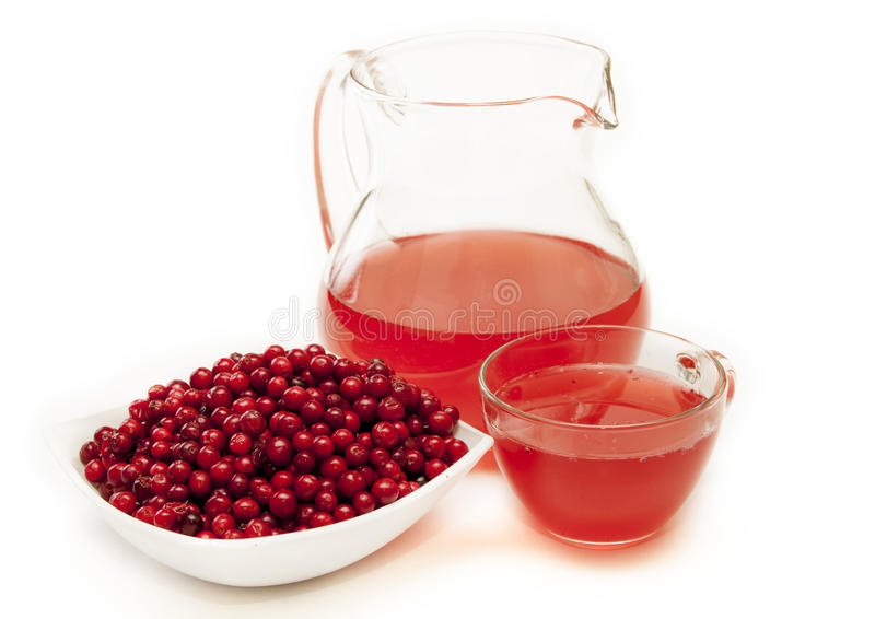 Juice in a jug and berries cranberries in a bowl. Juice in a jug and berries cranberries in a bowl on a white background stock image