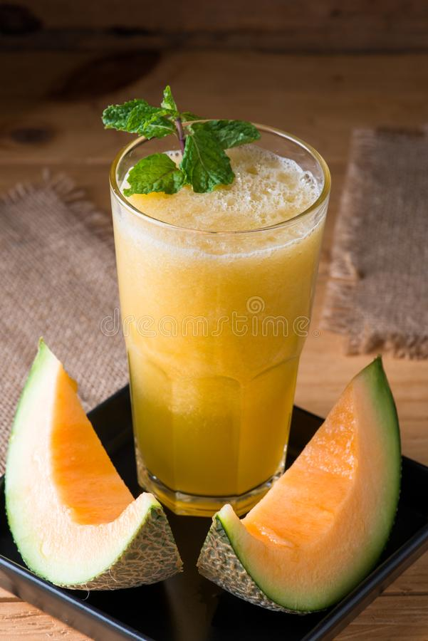 The juice of melon with mint in a glass on the table. Hami melon stock photography