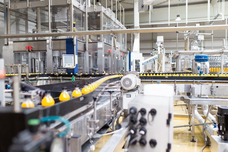 Juice and soda bottling factory. Bottling factory - Orange juice bottling line for processing and bottling juice into bottles. Selective focus stock images