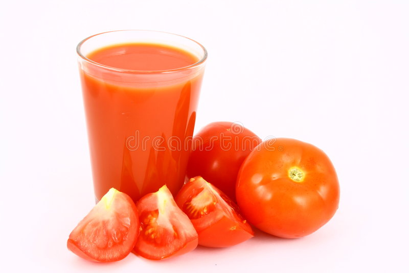 Juice tomato. Close-up of a few tomatoes and a glass of juice royalty free stock photography