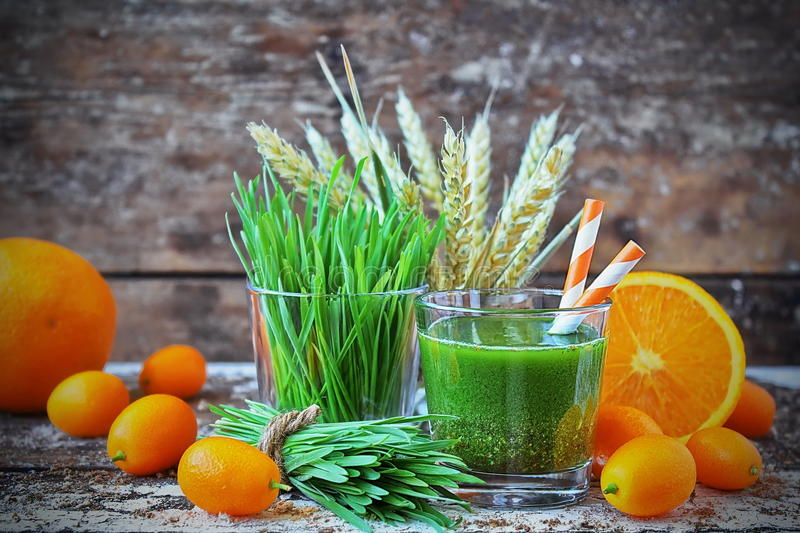 Juice Wheatgrass met sinaasappel in het glas stock foto