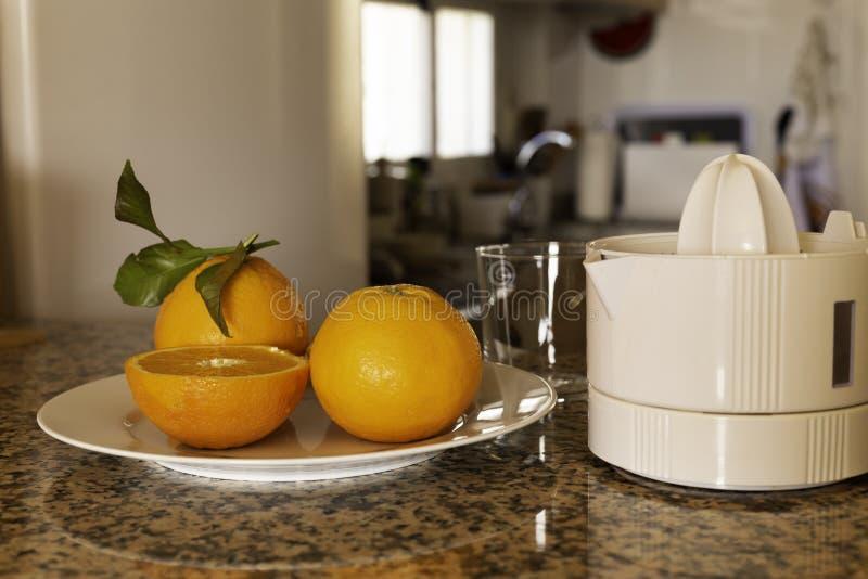 Juicer со свежо сжиманным апельсиновым соком и всеми и отрезанными апельсинами стоковые изображения rf