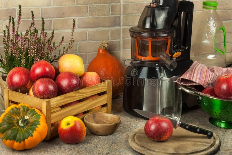 Juicer and apple juice. Preparing healthy fresh juices. Home juicing apples in the kitchen. Processing autumnal fruit. stock photography