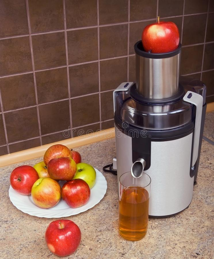 Juicer, apples, a glass of juice. On the kitchen table royalty free stock images