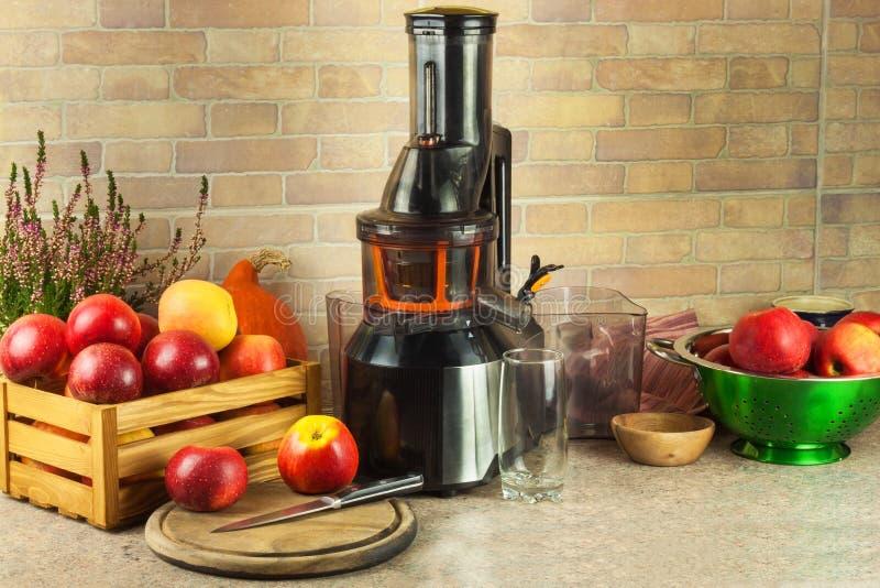 Juicer och äppelmust Förbereda sunda nya fruktsafter Hem- juicing äpplen i köket Bearbeta höstlig frukt arkivfoton