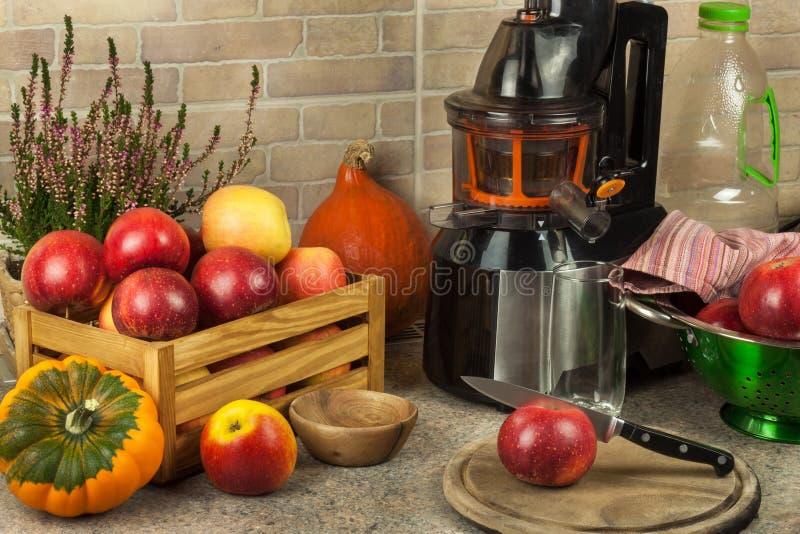Juicer und Apfelsaft Zubereitung von gesunden frischen Säften Juicing Hauptäpfel in der Küche Verarbeitung der herbstlichen Fruch stockfotografie