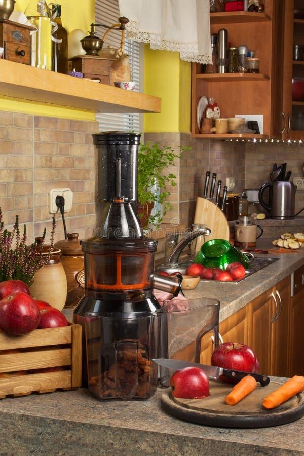 Juicer y zumo de manzana Preparación de los jugos frescos sanos Manzanas juicing caseras en la cocina Proceso de la fruta otoñal foto de archivo libre de regalías