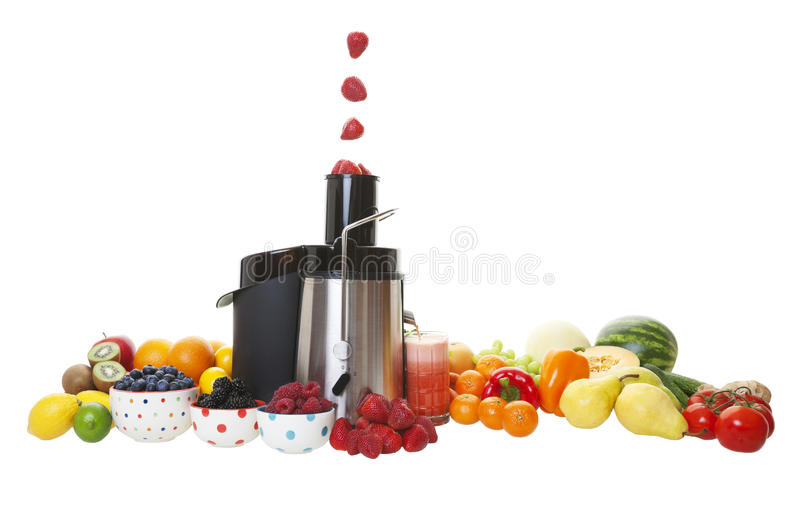 Juicing. Sweet, ripe strawberries fall into the juicing machine hopper, and the extracted juice flows into the glass. Shot on white background stock photos