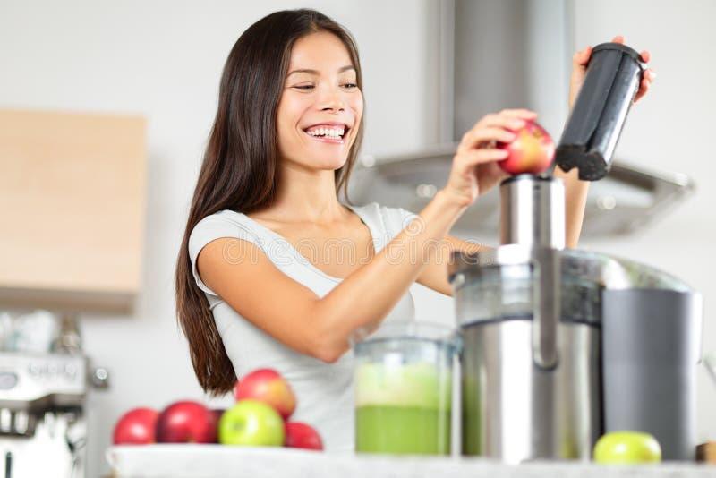 Juicing - Frau, die Apfel- und Gemüsesaft macht stockfotos