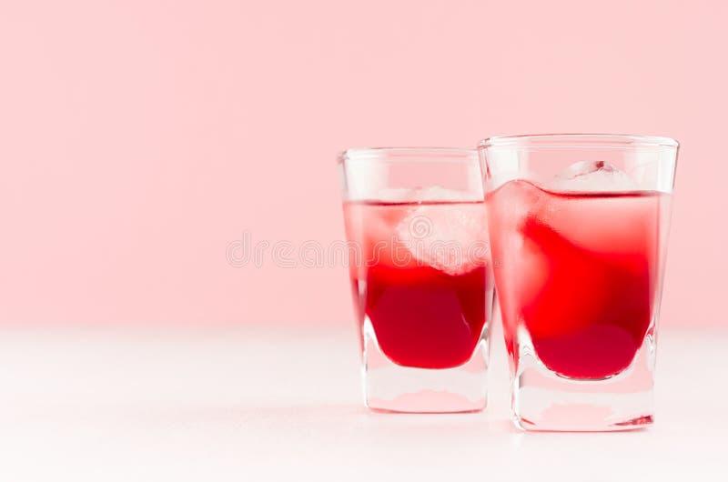 Juicy κόκκινα τροπικά κρύα κοκτέιλ φραουλών με τους κύβους πάγου σε δύο υγρά βλασταημένα γυαλιά στο λευκό ξύλινο πίνακα και το αν στοκ εικόνες