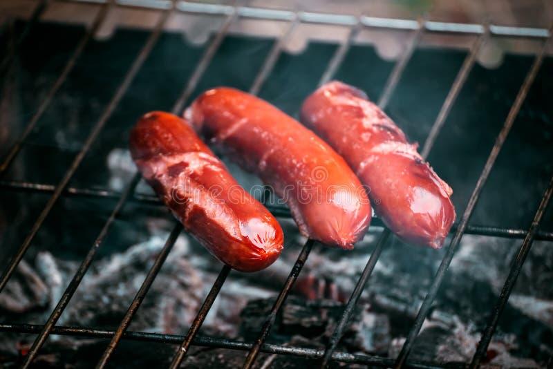Juicy λουκάνικα χοτ-ντογκ που μαγειρεύουν στην πυρκαγιά στοκ εικόνες με δικαίωμα ελεύθερης χρήσης