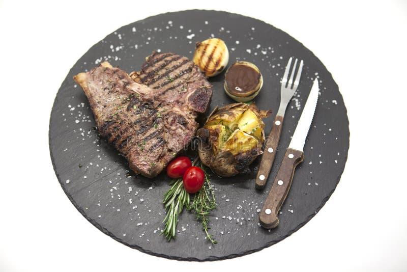 Juicy μέσος σπάνιος μπριζόλας βόειου κρέατος σε μια πέτρα έψησε τη σάλτσα πατατών και σχαρών και το μεγάλο άλας θάλασσας με το δί στοκ φωτογραφία με δικαίωμα ελεύθερης χρήσης