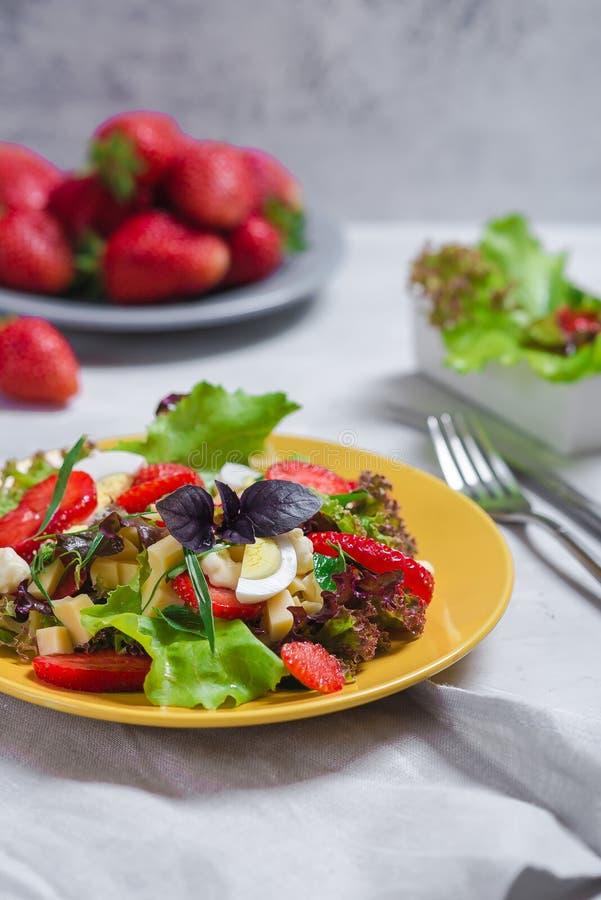 Juicy ορεκτικό με τη σαλάτα, τις φρέσκες φράουλες, το τυρί και το βασιλικό, και το αυγό στοκ εικόνες