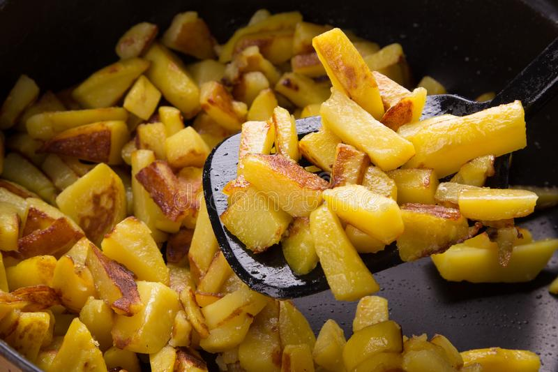 Juicy τηγανισμένες πατάτες τηγανίζοντας παν, σπιτικές ψημένες πατάτες με μια τριζάτη κρούστα κοντά επάνω στοκ εικόνες