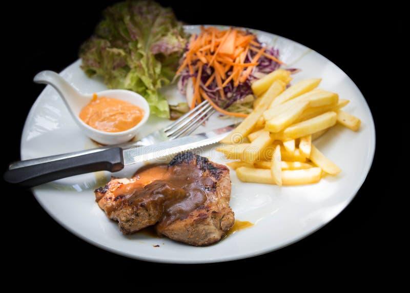 Juicy ψημένη στη σχάρα μπριζόλα χοιρινού κρέατος (λαιμός που κόβεται) με τα πράσινα στοκ φωτογραφίες