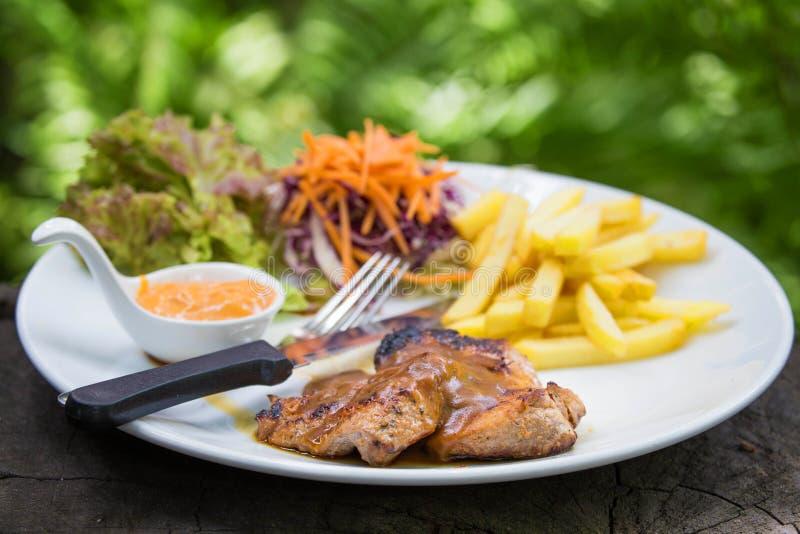 Juicy ψημένη στη σχάρα μπριζόλα χοιρινού κρέατος (λαιμός που κόβεται) με τα πράσινα στοκ φωτογραφία