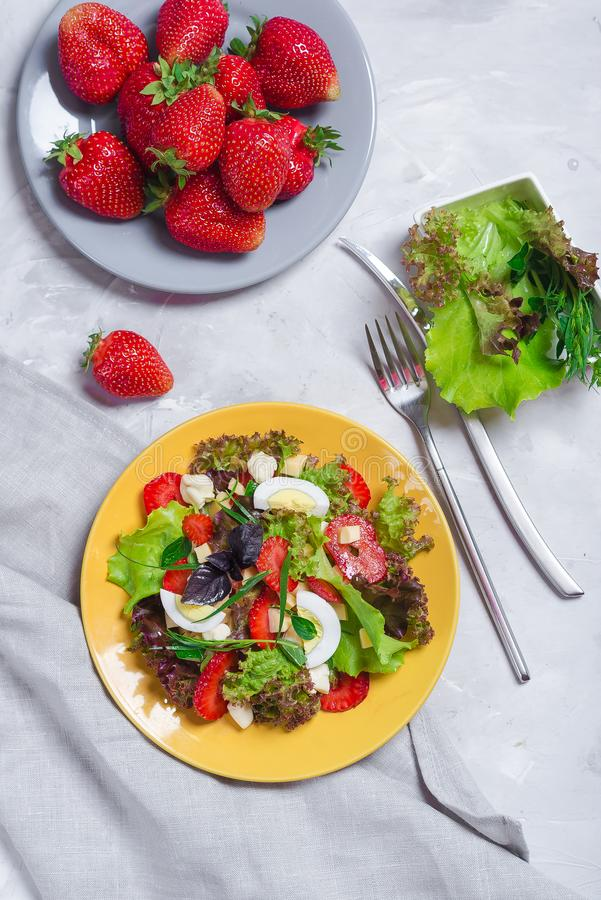 Juicy appetizer with crispy salad, strawberries, cheese and basil, and egg. royalty free stock photos