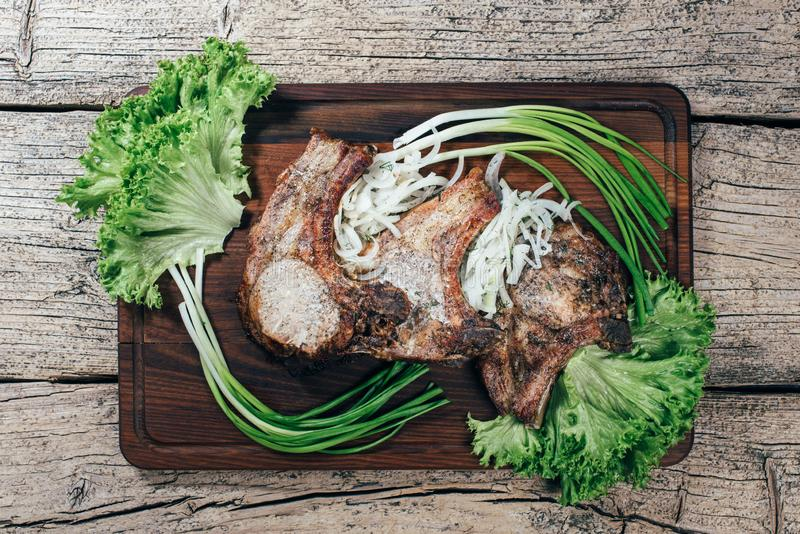 Juicy, appetizing pork steak is presented on a wooden board with green onions and lettuce leaves stock image