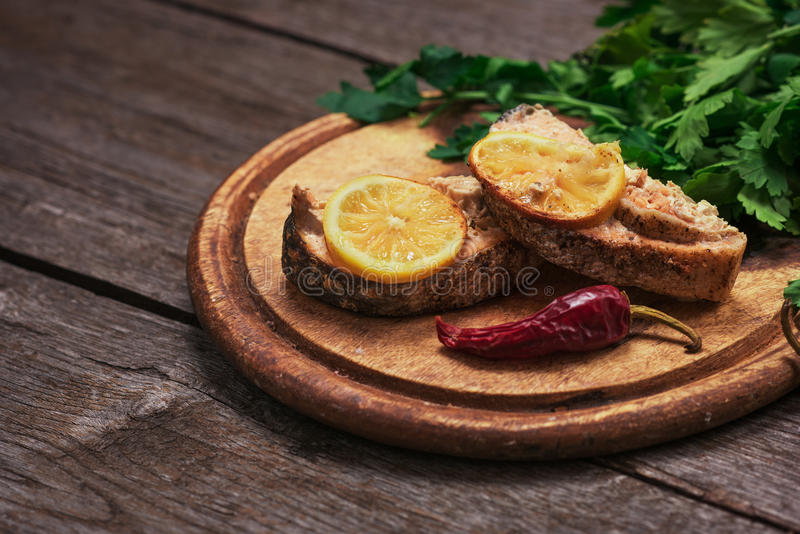 Juicy baked salmon with lemon and herbs royalty free stock photo