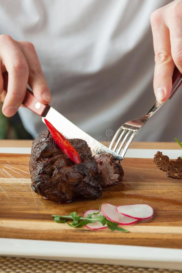 Beef fillet Mignon medium roasting on a wooden Board. Juicy beef fillet Mignon medium roasting on a wooden Board royalty free stock images