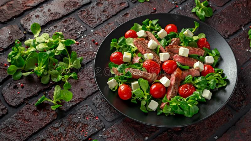 Juicy Beef Sirloin Steak Salad with roasted tomatoes, feta cheese and green vegetables in a black plate. healthy food stock image