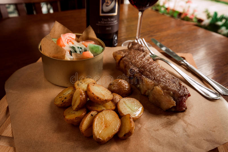 Juicy beef steak with potatoes and wine royalty free stock images