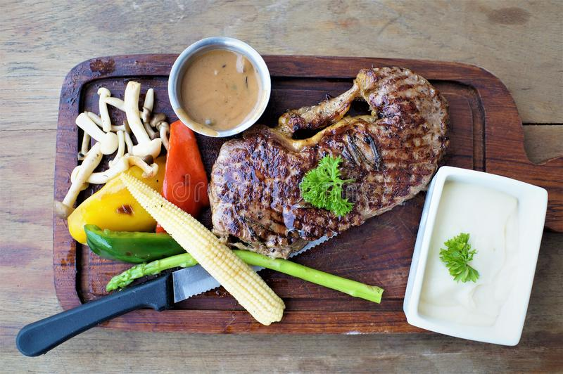 Juicy beefsteak with boiled vegetable on the wooden plate stock photo