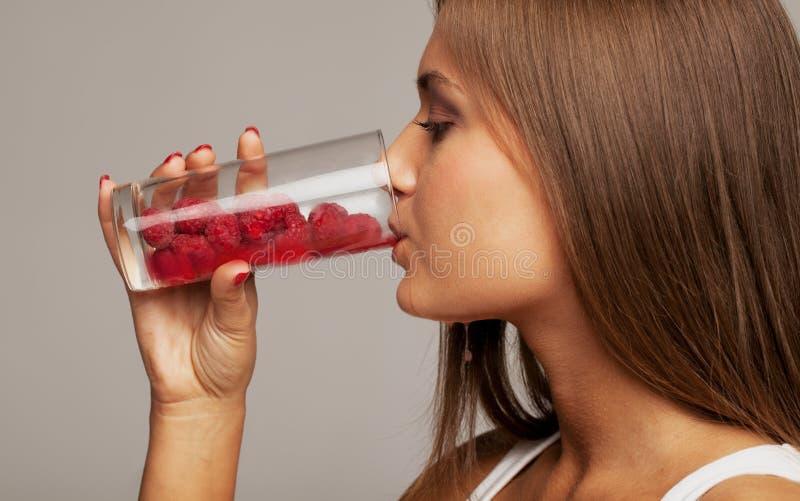Juicy berries. Girl with glass of juicy berries stock photography