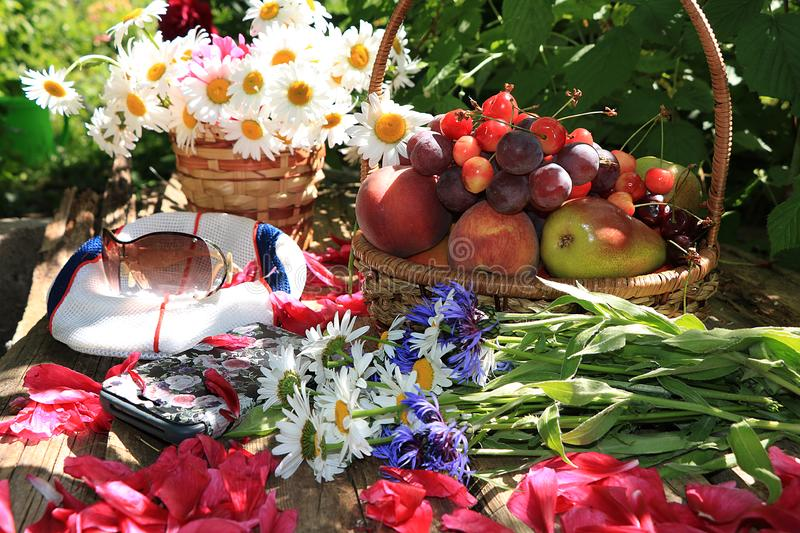 Juicy black grapes and apples, pears and peaches in a basket in the garden on an old wooden table, stock image